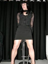 Black haired crossdressing beauty in sleek black dress